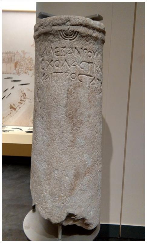 """Αρχαιολογικό εύρημα - κιονίσκος - με σύμβολο της επτάφωτης λυχνίας και επιγραφή """"ΑΛΕΞΑΝΔΡΟΥ ΣΧΟΛΑΣΤΙΚΟΥ ΚΑΙ ΠΡΟΣΤΑΤΟΥ"""""""