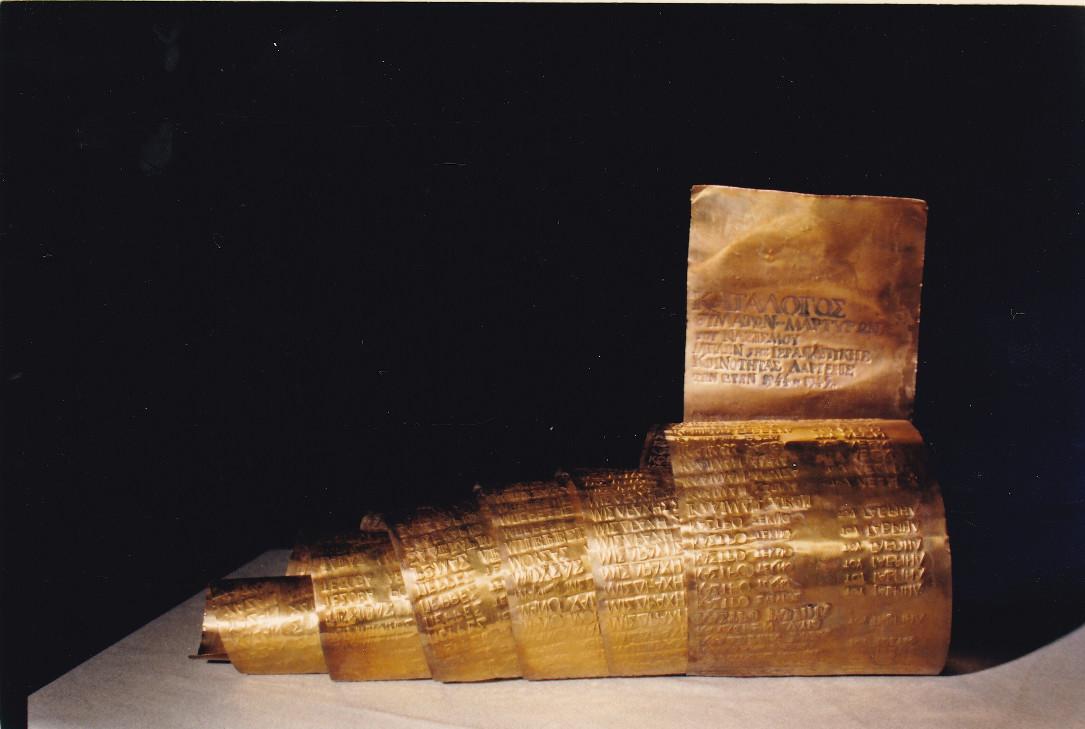 Κύλινδρος από χαλκό με χαραγμένα τα ονόματα των Λαρισαίων που χάθηκαν στο Ολοκαύτωμα. Φυλάσσεται σε ειδική κοιλότητα στη βάση του μνημείου.